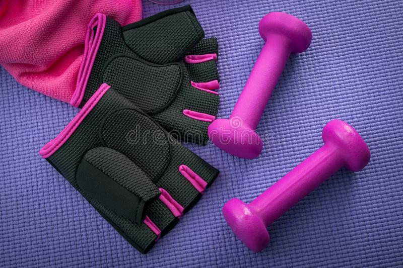 Healthy lifestyle, fitness and yoga concept with girly workout equipment like a pink pair of gym gloves, two dumbbells or weights stock photo