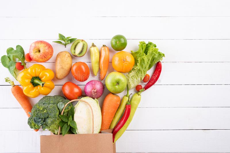 Healthy lifestyle and food concept. Top view paper bag of different fresh vegetables on white wooden background. Flat lay stock photography