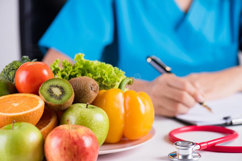 Healthy lifestyle, food and nutrition concept. Close up of fresh vegetables and fruits with stethoscope lying on doctor`s desk stock photos