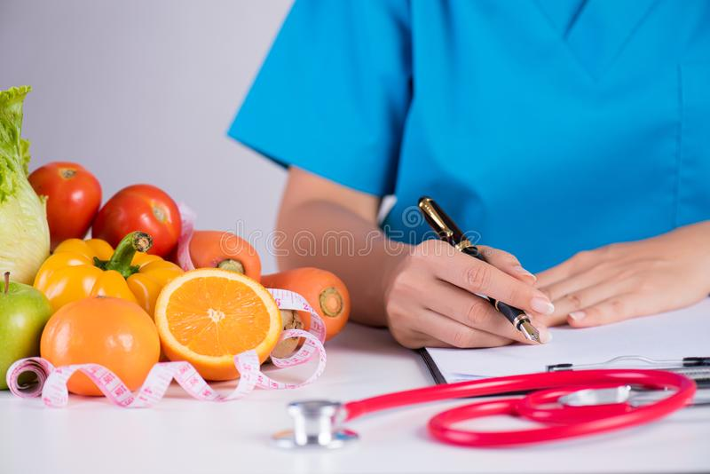 Healthy lifestyle, food and nutrition concept. Close up of fresh vegetables and fruits with stethoscope lying on doctor`s desk.  royalty free stock photos