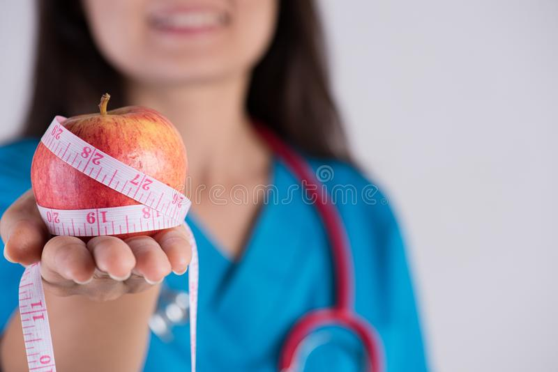 Healthy lifestyle, food and sport concept. Close up Smiling doctor woman hand holding measuring tape around fresh green apple stock image