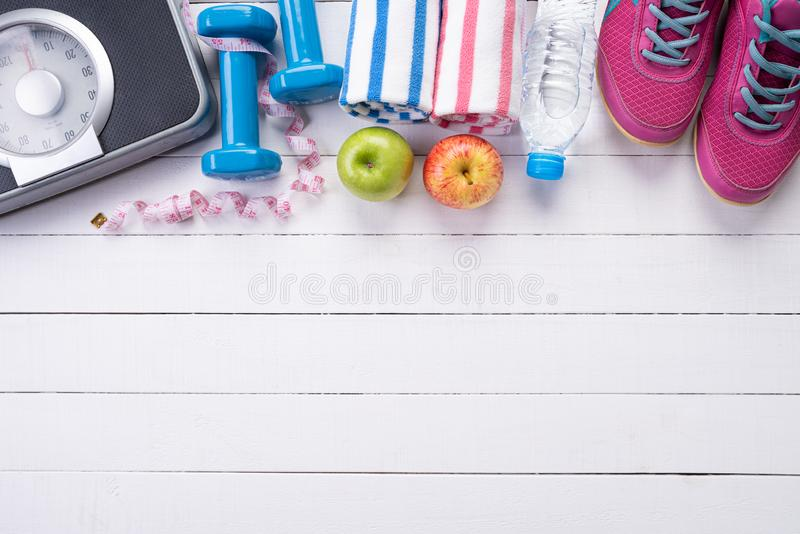 Healthy lifestyle, food and sport concept. Top view of athlete`s equipment Weight Scale measuring tape blue dumbbell, sport water stock photos