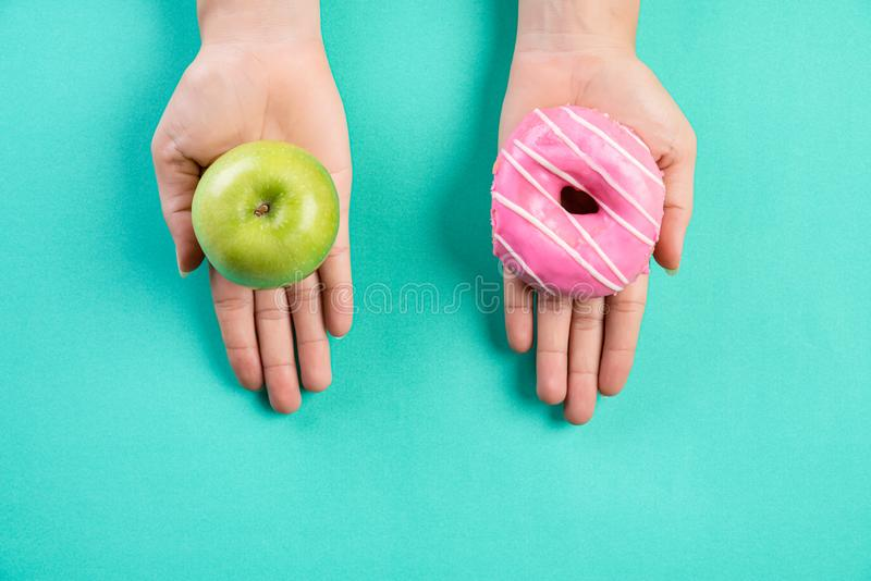 Healthy lifestyle, food and sport concept. Top view of healthy versus unhealthy. Woman hand holding donut and green apple on blue stock photo