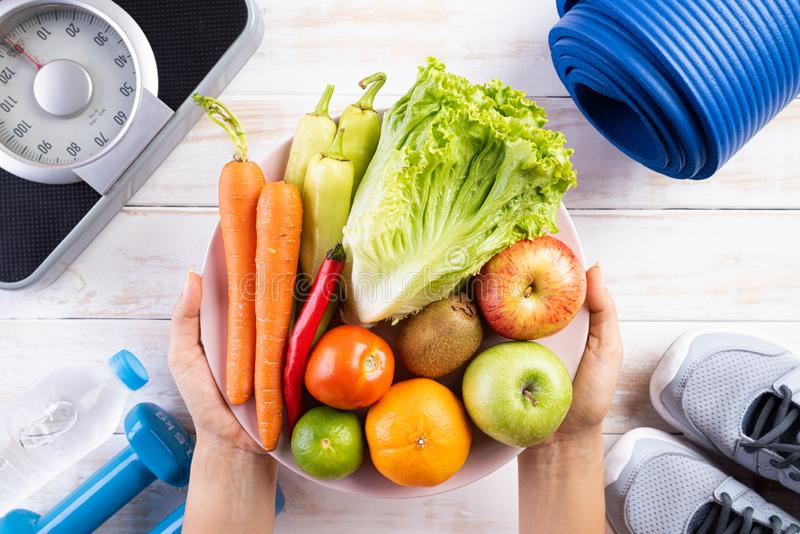 Healthy lifestyle, food and sport concept. Top view of woman hand holding plate of fresh vegetables and fruits with athlete`s. Equipment Weight Scale blue stock photo