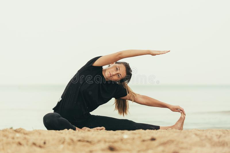 Healthy lifestyle: a girl practices yoga by the sea in cloudy weather. Healthy lifestyle: girl practices yoga by the sea in cloudy weather royalty free stock photo