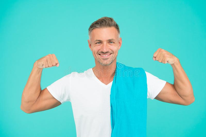 Healthy lifestyle. Gym wear and sports fashion for men. Gym aesthetics. Man well groomed athlete with towel on blue royalty free stock images