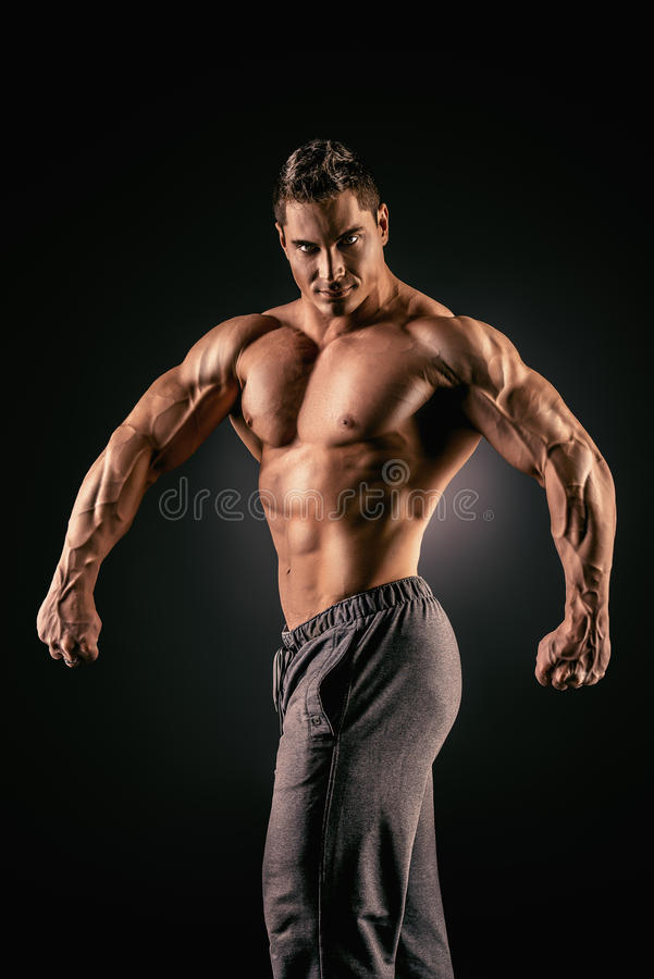 Healthy lifestyle. Handsome muscular bodybuilder posing over black background stock images