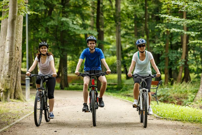 Healthy lifestyle - happy people riding bicycles in city park stock photos
