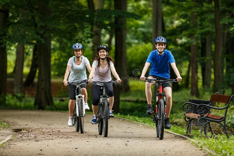 Healthy lifestyle - happy people riding bicycles in city park. Healthy lifestyle - people riding bicycles in city park stock photography