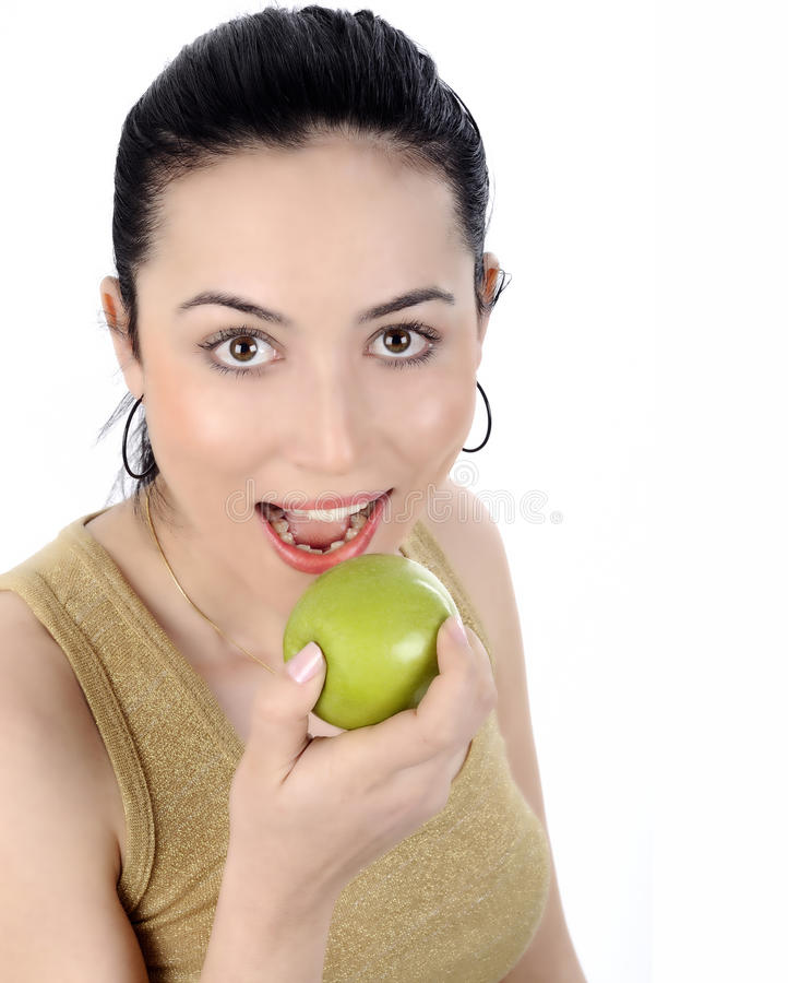 Healthy Lifestyle - Happy woman eating an apple. Young beautiful woman eating green apple isolated over white background stock image