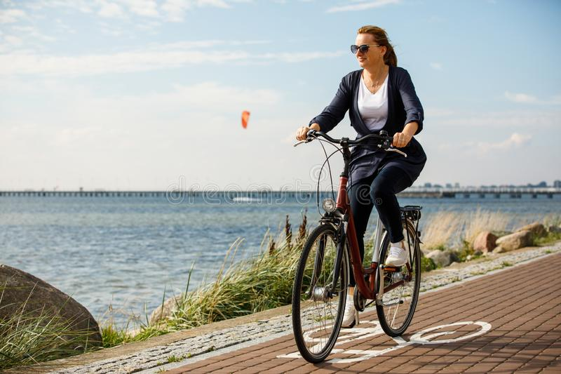 Healthy lifestyle - middle-aged woman riding bicycles. Healthy lifestyle - happy woman riding bicycle royalty free stock images