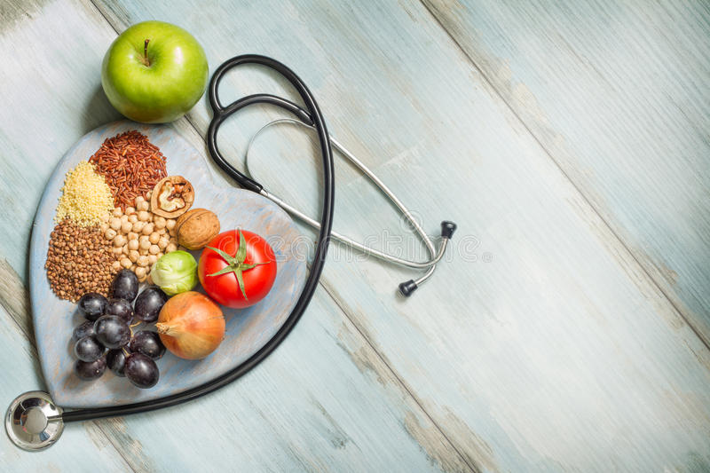 Healthy lifestyle and healthcare concept with food, heart and stethoscope stock photo