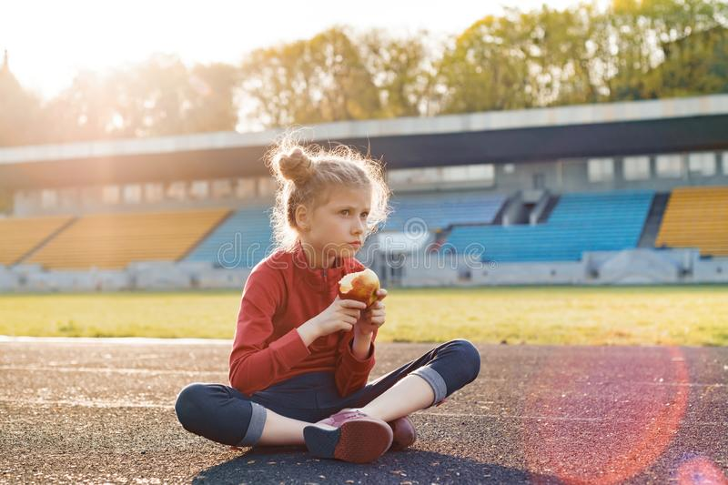 Healthy lifestyle and healthy food concept. Little beautiful girl child in sportswear eating apple sitting on stadium after. Training on sunny spring day royalty free stock photo