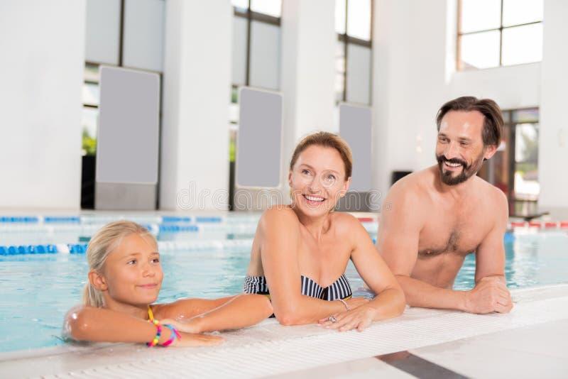 Joyful nice family visiting an indoor pool royalty free stock photography