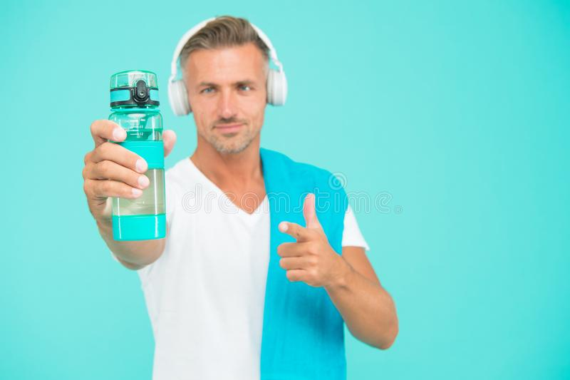 Healthy lifestyle. Man well groomed athlete with towel. Sportsman gym instructor with water bottle and headphones. Gym royalty free stock photo