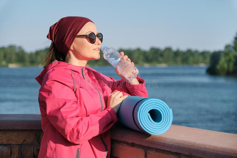 Healthy lifestyle of mature woman, outdoor portrait of an age female in sportswear with yoga mat, drinking water from bottle royalty free stock photography