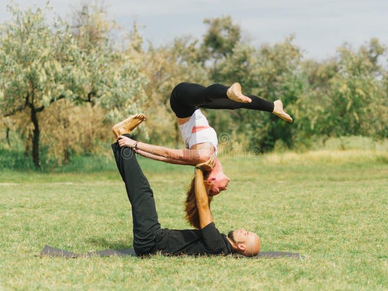 Healthy lifestyle modern activity. Young couple doing acro bird yoga pose. stock image