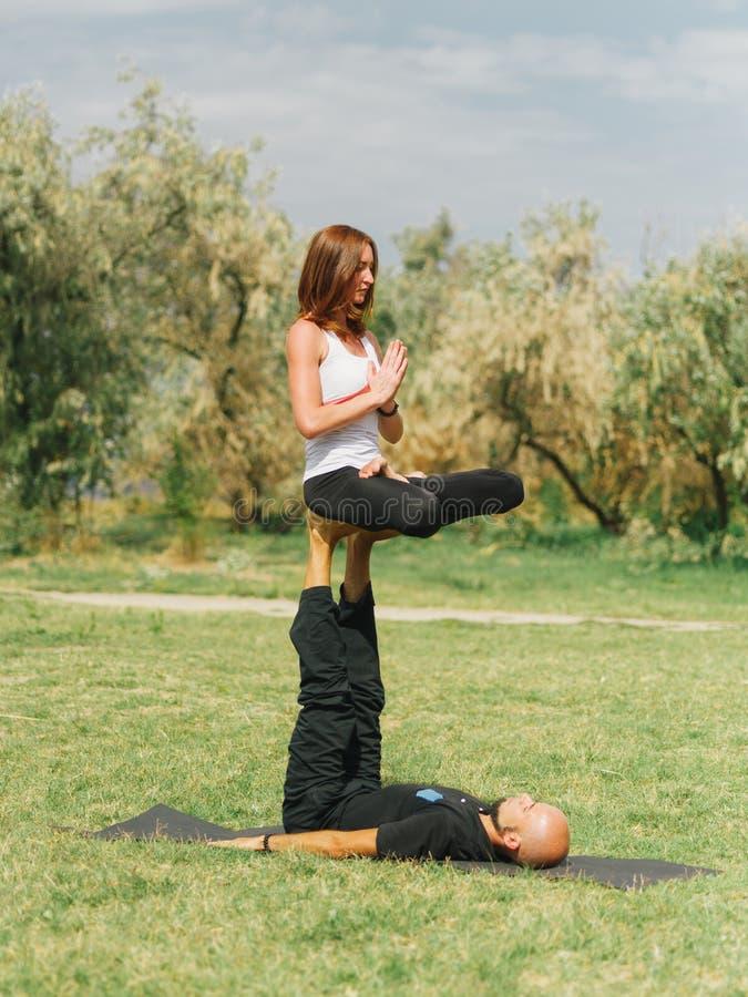 Healthy lifestyle modern activity. Young couple doing acro bird yoga pose. stock photo