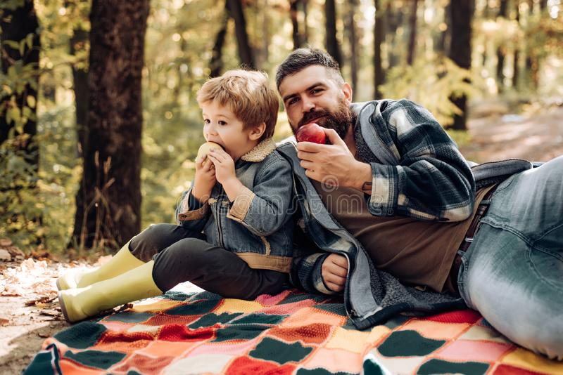 Healthy lifestyle. Nature picnic. Healthy snack. Vitamin charge. Family picnic. Hipster bearded dad with son spend time royalty free stock image