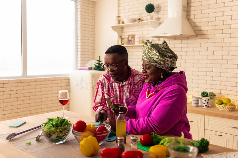Nice delighted couple cooking healthy food together stock photography