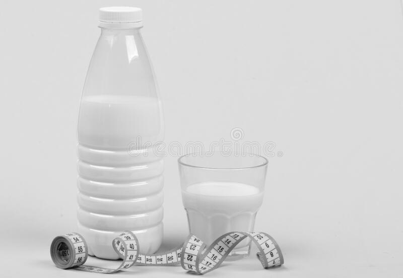 Healthy lifestyle and nourishment concept. Calcium nutrition and healthy diet. Milk in transparent containers. Wrapped with rolled tape. Bottle and glass of royalty free stock photography