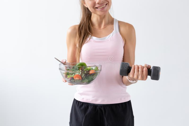 Healthy lifestyle, people concept - a plate of salad in one hand and dumbbell in another hand. Smile and fitness suit.  stock photo