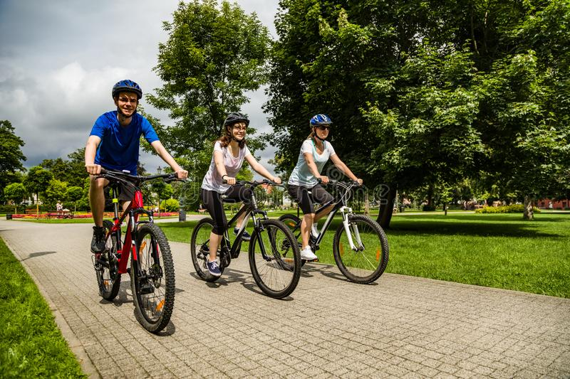 Healthy lifestyle - people riding bicycles in city park. Healthy lifestyle - happy people riding bicycles in city park stock image