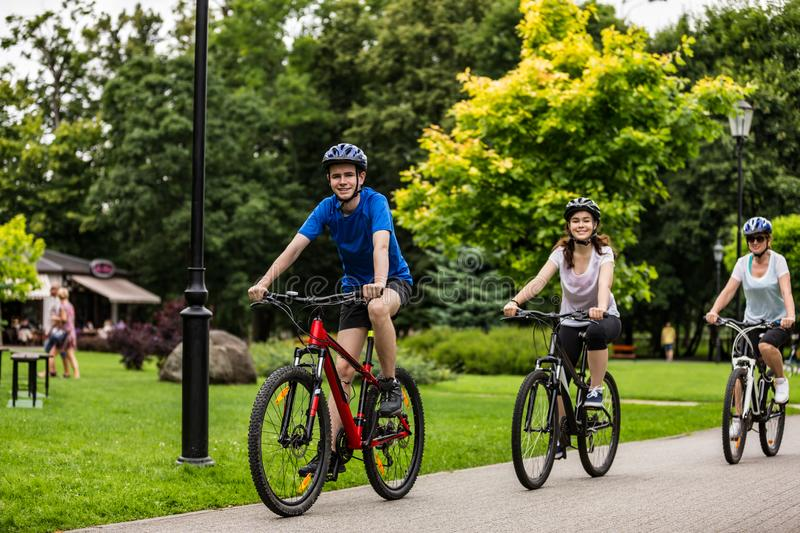 Healthy lifestyle - people riding bicycles in city park. Healthy lifestyle - happy people riding bicycles in city park stock photos