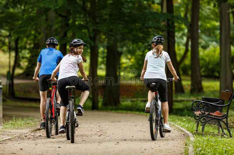 Healthy lifestyle - people riding bicycles in city park. Healthy lifestyle - happy people riding bicycles in city park royalty free stock photo