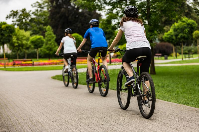 Healthy lifestyle - people riding bicycles in city park. Healthy lifestyle - happy people riding bicycles in city park stock photography