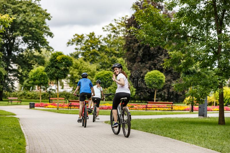 Healthy lifestyle - happy people riding bicycles in city park royalty free stock image
