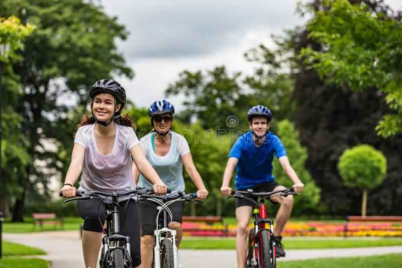 Healthy lifestyle - happy people riding bicycles in city park stock photo