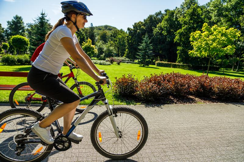 Healthy lifestyle - people riding bicycles in city park royalty free stock image