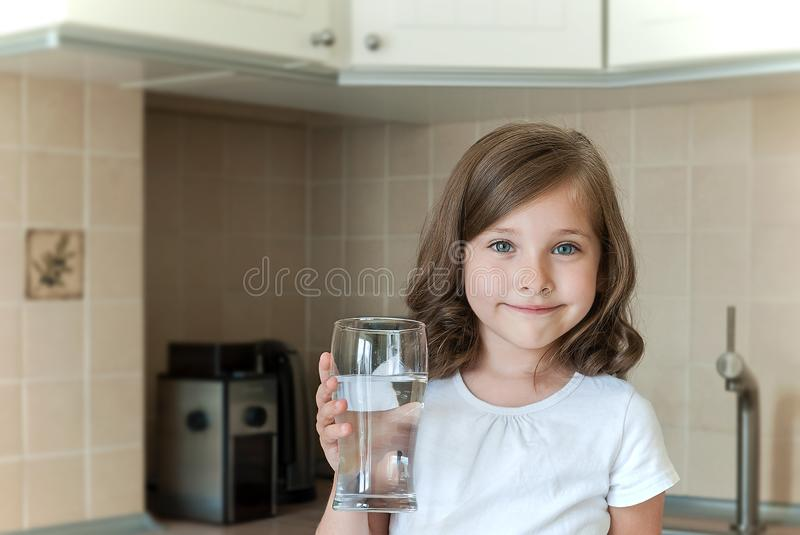 Healthy lifestyle. Portrait of happy smiling girl with glass. Child drinking water in the kitchen. Health, beauty, diet concept royalty free stock images