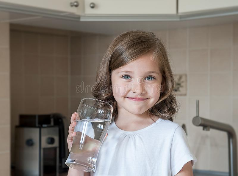 Healthy lifestyle. Portrait of happy smiling young girl with glass. Child drinking fresh water in the kitchen at home royalty free stock photo