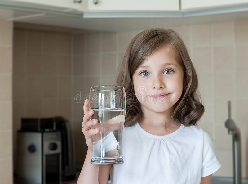 Healthy lifestyle. Portrait of happy smiling young girl with glass. Child drinking fresh water in the kitchen at home royalty free stock images