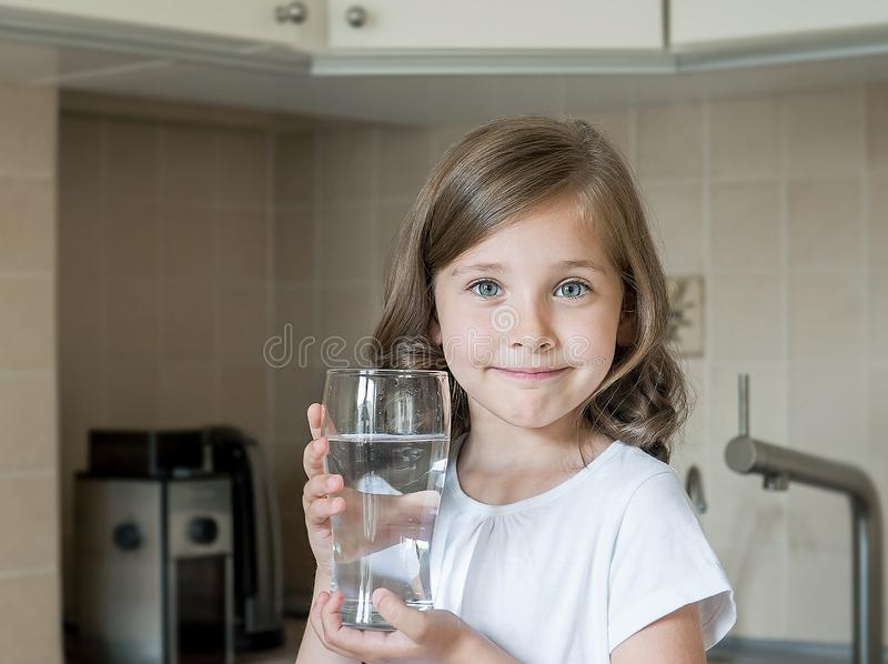 Healthy lifestyle. Portrait of happy smiling young girl with glass. Child drinking fresh water in the kitchen at home. Health royalty free stock images