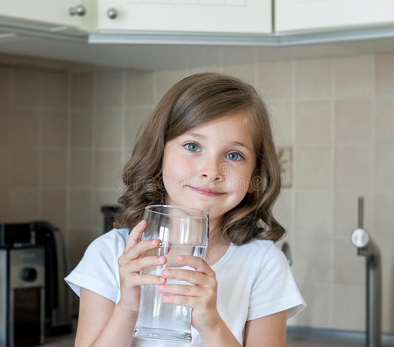 Healthy lifestyle. Portrait of happy smiling young girl with glass. Child drinking fresh water in the kitchen at home. Healthcare stock photo