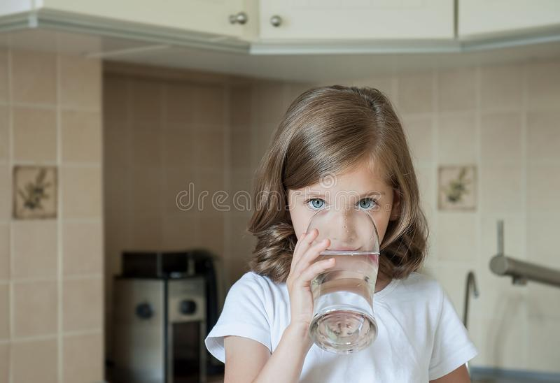 Healthy lifestyle. Portrait of happy smiling young girl with glass. Child drinking fresh water in the kitchen at home. Healthcare stock image