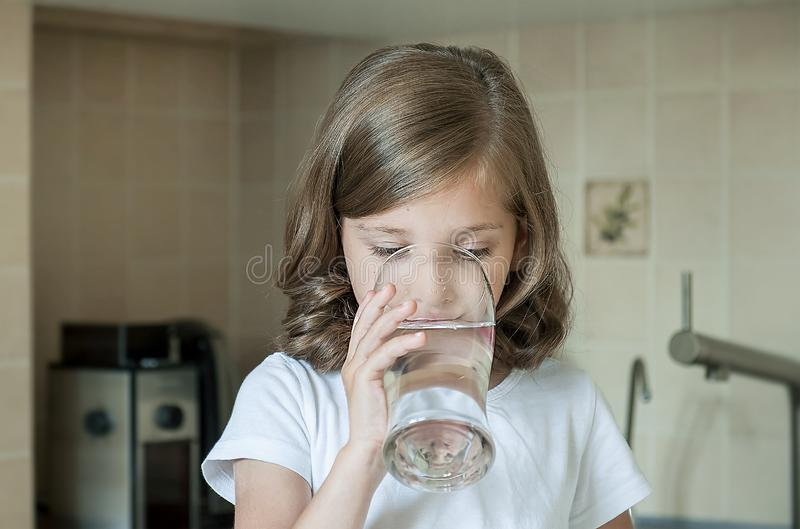 Healthy lifestyle. Portrait of happy young girl with glass. Handsome child drinking fresh water in the kitchen at home royalty free stock photos