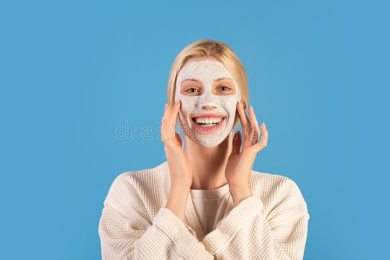 Healthy lifestyle and self care. Girl chilling making clay facial mask. Skin health. Woman adorable pretty smiling girl. With clay mask. Cleaning and care for stock photo