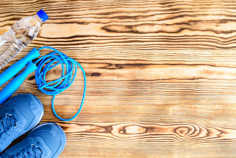 Healthy lifestyle and sport background. Sport shoes, skipping rope and bottle of water on the wooden background with copyspace, t. Op view, flat. Sport equipment stock photography