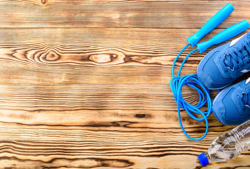 Healthy lifestyle and sport background. Sport shoes, skipping rope and bottle of water on the wooden background with copyspace, t. Op view, flat. Sport equipment stock photos