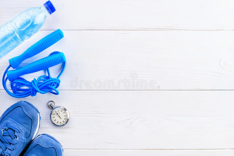 Healthy lifestyle and sport background. Sport shoes, skipping rope, stopwatch and bottle of water on the light wooden background. With copyspace, top view, flat royalty free stock photo