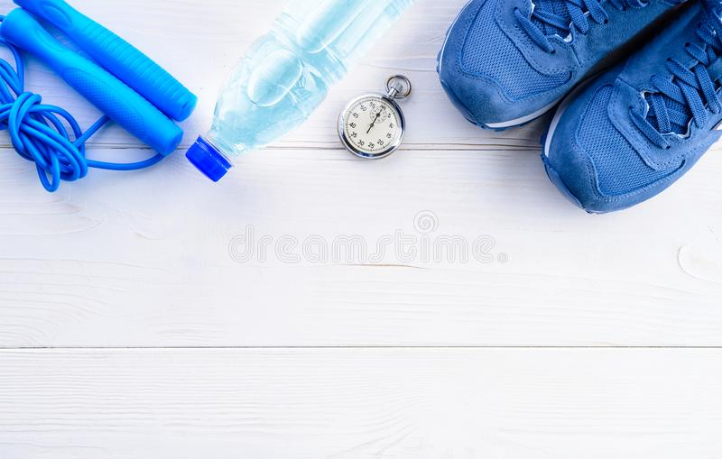 Healthy lifestyle and sport background. Sport shoes, skipping rope, stopwatch and bottle of water on the light wooden background. With copyspace, top view, flat royalty free stock photography