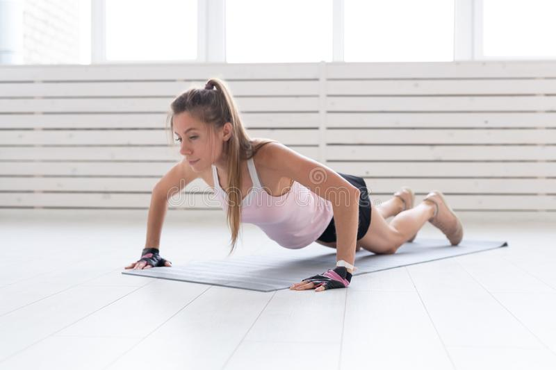 Healthy lifestyle, sport, people concept - a young woman is doing fitness in the gym or home. She is pressing in the. Sport suit royalty free stock photography