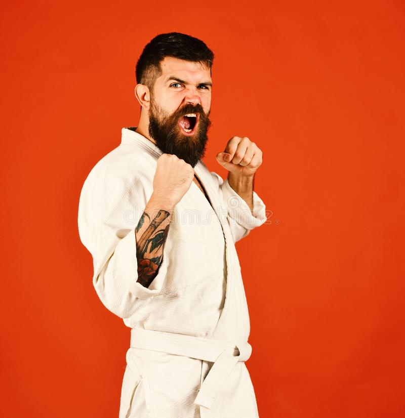 Healthy lifestyle and sports concept. Jiu Jitsu master. Practices attack or defense posture showing fists. Man with beard in white kimono on red background stock photo