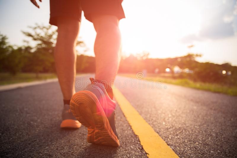 Healthy lifestyle sports a man legs running and walking. While exercising outdoors during sunrise or sunset. Moving forward to success concept stock photo