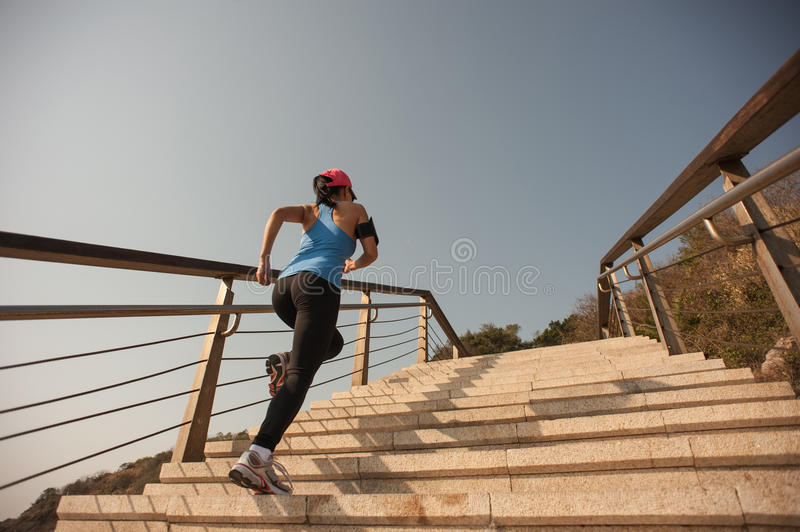 Healthy lifestyle sports woman running. Up on stone stairs seaside royalty free stock image