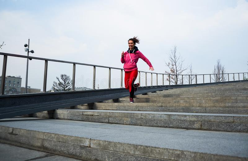 Healthy lifestyle sports woman running up on stone stairs at sunrise seaside stock photo